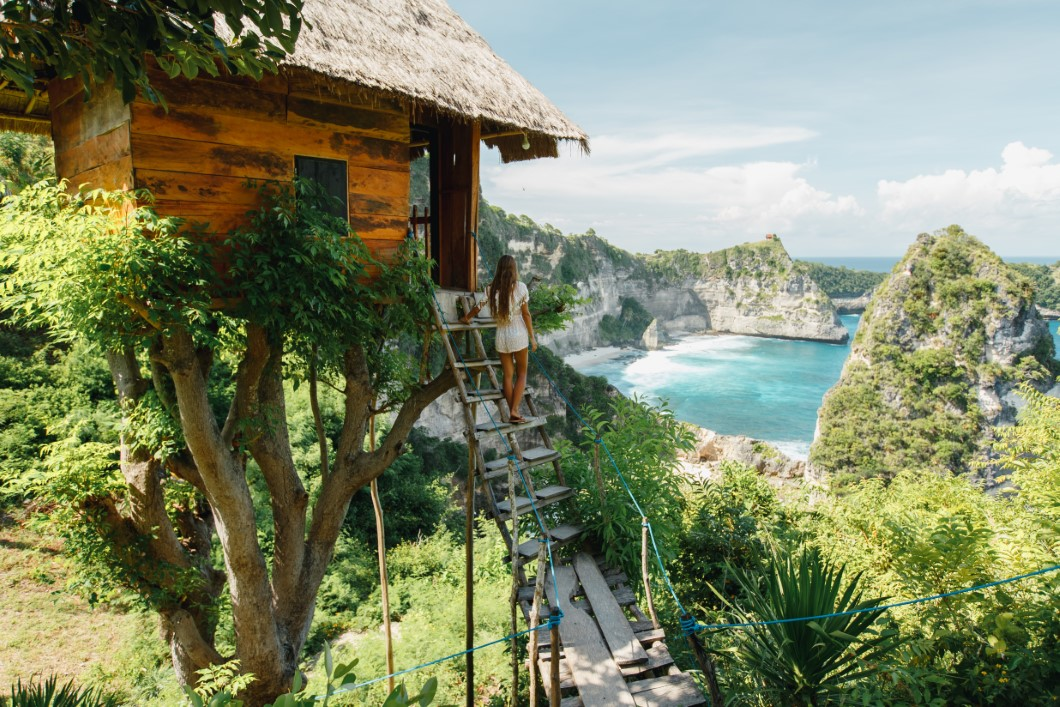 Young girl on steps of traditional house on tree, look at Atun beach, Nusa Penida island. Popular travel destination on Bali holidays. Indonesian background.  travel lifestyle convet